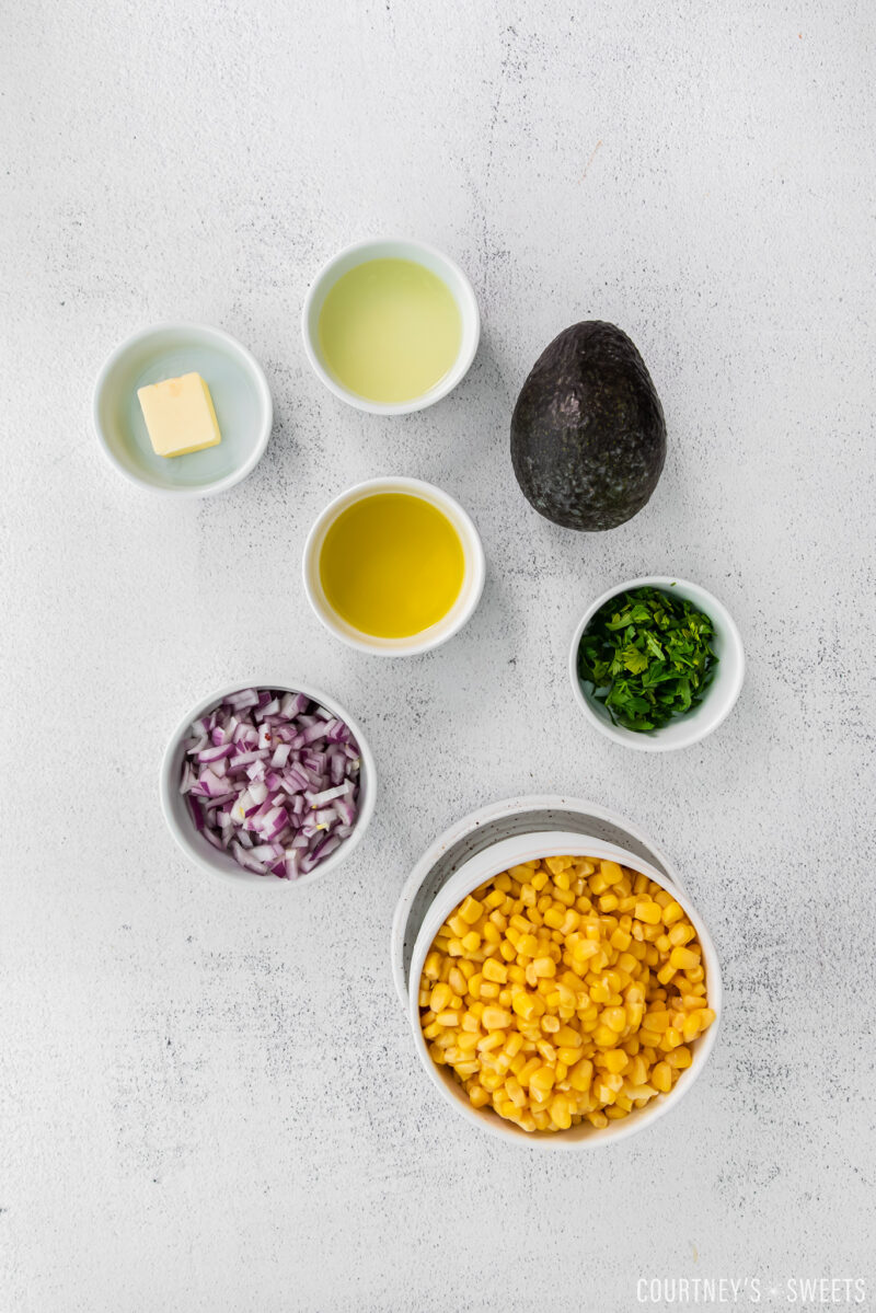 ingredients for avocado corn salsa in small bowls on cement backdrop