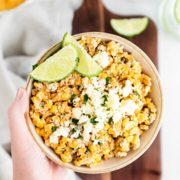 hand holding elote corn dip in low bowl