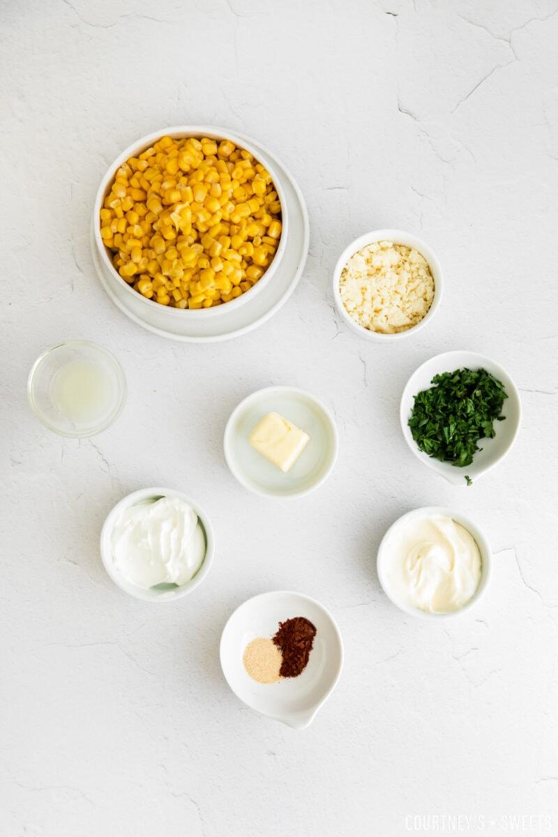 elote dip ingredients in small bowls on gray slab